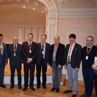 Spaudos konferencijai Palangos kurhauze pasibaigus su XVIII-ojo Lietuvos pučiamųjų instrumentų orkestrų čempionato svečiais, žiuri vertinimo komisijos nariais ir organizatoriais. Iš kairės į dešinę: Remigijus Vilys, Rimantas Antanas Mikalkėnas, Brett Baker, Kazys Daugėla, Jacob Dijkstra, Tom Davoren, Vygantas Rekašius  ir Viktorija Puidokė.